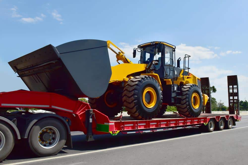 Transporting a bulldozer usine a tilt tray tow truck in Alice Springs